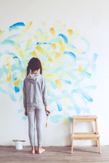 Little girl painting on a wall